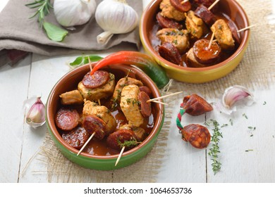 Hot Spanish snack: Braised pork fillet with fried slices of chorizo paprika sausage