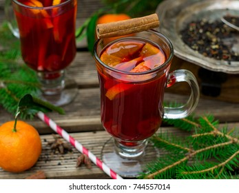 Hot spiced drink from infused tea with rum, cherries and mandarin