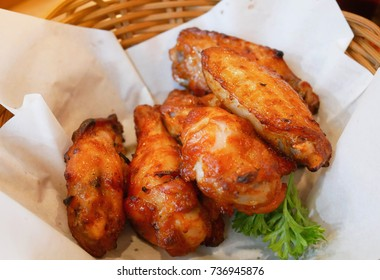 Hot and spicy BBQ chicken wings on brown wooden basket. It's delicious can be use for food concept.