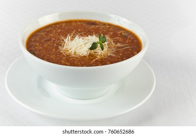hot and spicy beef soup with cheese in a bowl on white background
