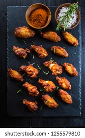 Hot and spicy chicken wings with spices on dark background