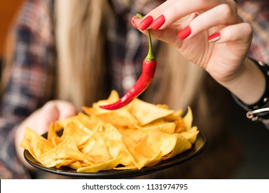 hot spicy chips. pungent fiery food snack. woman hand holding nacho crisps and red chili pepper