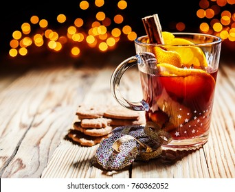 Hot spicy Christmas gluhwein, or mulled red wine with sugar and spices, served with cookies on rustic wood with a twinkling bokeh of party lights in the background