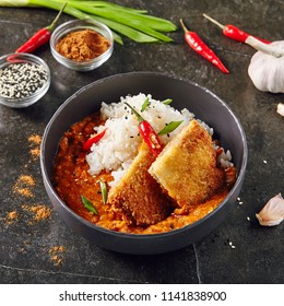 Hot Spicy Crispy Fried Chicken Fillet with Curry and Rice on Dark Background. Katsu or Tonkatsu with Red Peppres, Turkey Meat Cutlet in Breadcrumbs, Tomatoes, Chilli Sauce, Sesame, Greens and Herbs