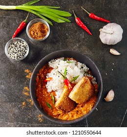 Hot Spicy Crispy Fried Chicken Fillet with Curry and Rice on Dark Background Top View. Katsu or Tonkatsu with Red Peppres, Turkey Meat Cutlet in Breadcrumbs, Tomatoes, Chilli Sauce, Sesame