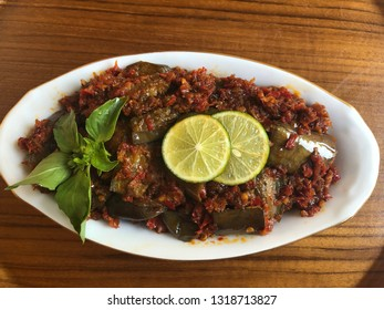 hot spicy eggplant close up view with green vegetable and slice lemon