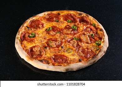 Hot spicy fresh baked pizza with salami and green jalapeno slices in crusty cheese on black marble background