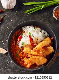 Hot Spicy Fried Shrimps with Curry and Rice in Black Bowl. Crispy Prawns in Breadcrumbs with Red Peppres, Tomatoes, Chilli Sauce, Sesame, Green Onion and Herbs