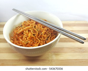 Hot and Spicy Korean Samyang ramen noodles in white bowl on wooden board