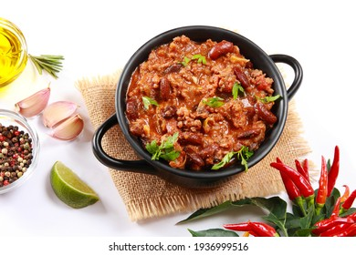 Hot and spicy Mexican Chilli Con Carne, with beef minced or pulled, rich savory sauce with fresh chillies served in bowl on white background with copy space available