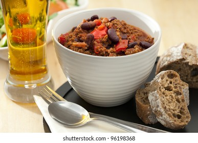 Hot and spicy minced meat chili with fresh bread and cold beer