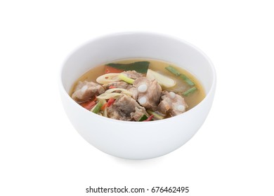 hot and spicy pork rib soup with Thai herbs in ceramic bowl isolated on white background with clipping path and soft shadows