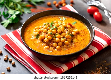 Hot spicy soup with chickpeas, onions, and tomato in a black ceramic bowl on a dark background close-up. Tasty vegetarian food, Indian dish.