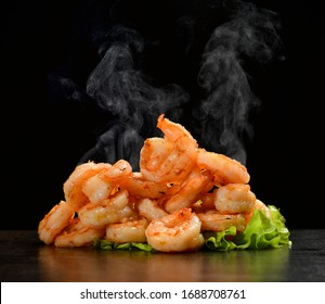 Hot and spicy sweet and sour prawns shrimp with steam smoke on black background