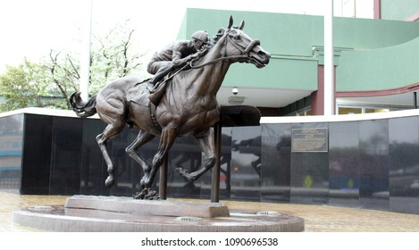 Hot Springs, AR/USA: April 1, 2018 – Statue of 2015 Triple Crown Winner named American Pharoah is at entrance to Oaklawn Park Racetrack and Casino, where he made his debut as a 3 year old colt.