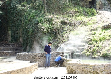 Hot Springs, AR/USA: March 30, 2018 – Man watches boy take photo of natural steaming water feature and rock ledge in Hot Springs National Park. Cascading ivy and stone steps in background.
