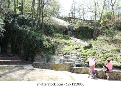 Hot Springs, AR/USA: March 30, 2018 – Two women with baby in stroller relax on stone ledge near natural steaming water feature in Hot Springs National Park. Cascading ivy and stone steps in background