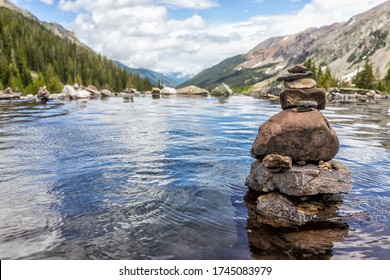 Hot springs pool and rock stack cairn on Conundrum Creek Trail in Aspen, Colorado in 2019 summer with valley view with nobody