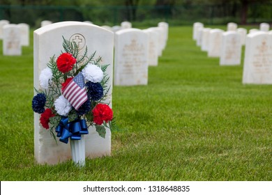 HOT SPRINGS, SOUTH DAKOTA - June 8, 2014:  A group of flowers resting on a headstone with rows of graves in the background at Hot Springs National Cemetery in Hot Springs, SD on June 8, 2014.