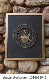 HOT SPRINGS, SOUTH DAKOTA - June 8, 2014:  A metal sign for the Veterans Administration on a rock masonry wall marking the entrance to Hot Springs National Cemetery in Hot Springs, SD on June 8, 2014.