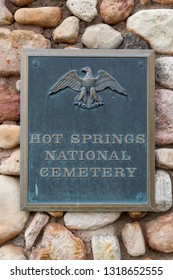 HOT SPRINGS, SOUTH DAKOTA - June 8, 2014:  A metal sign attached to a rock masonry wall marking the entrance to Hot Springs National Cemetery in Hot Springs, SD on June 8, 2014.