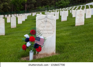 HOT SPRINGS, SOUTH DAKOTA - June 8, 2014:  A group of flowers resting on a headstone of a soldier of the Spanish American War at Hot Springs National Cemetery in Hot Springs, SD on June 8, 2014.
