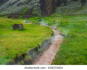 hot staeming spring stream at Reykjadalur valley with lush green grass meadow and hills. South Iceland near Hveragerdi city. Summer sunny day