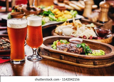 Hot steak with tomatoes, salad, zucchini, greens and sauce on a wooden board. Two glasses of dark beer. Beer table in the restaurant