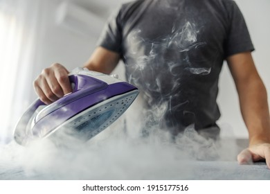 The hot steam from the iron. Powerful film effect of steam on photography. A close-up of a man's body in a grey t-shirt ironing clothes on an ironing board