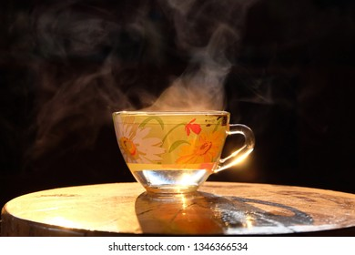 Hot steam on a cup of hot coffee and sunlight in the morning on a wooden table background