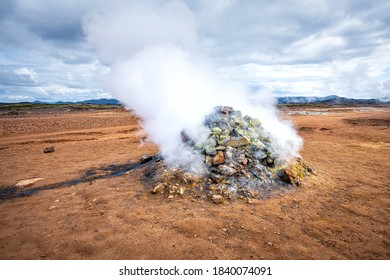 Hot steam rising from pile of rocks geyser in Hverir geothermal spot area in Iceland by Myvatn caldera lake famous place in north Iceland