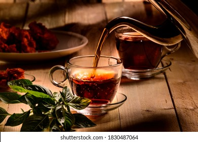 Hot steaming black tea in  a cup on a  rustic background