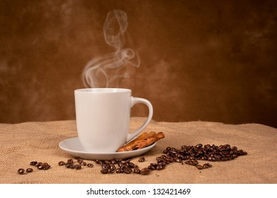 A hot, steaming coffee drink with cinnamon sticks on burlap with room for copy on the backdrop.
