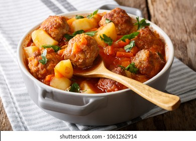 Hot stew meatball soup with vegetables in tomato sauce closeup in a pot on the table. horizontal