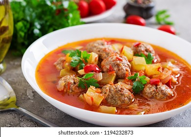 Hot stew tomato soup with meatballs and vegetables closeup in a bowl on the table. Albondigas soup, spanish and mexican food.