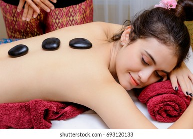 Hot stone massage therapy,Young woman getting hot stone massage in spa salon