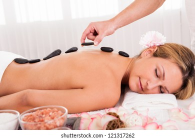 Hot stones lined on her back promotes relaxation.