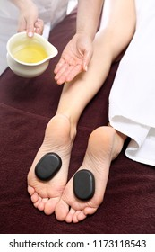 Hot stones massage. Female feet with basalt stones, relaxing in the spa salon.