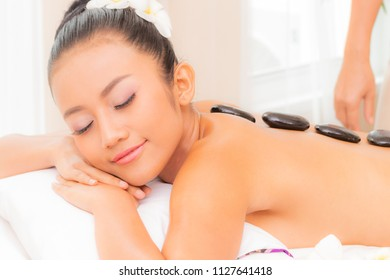 Hot Stones and Massage in Spa for Back Pain Relief and Relaxation and Massage spa Asia girl in Spa for Back Pain Relief and Relaxation.relaxing back massage in a spa center.