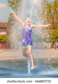 Hot summer in the city - girl is jumping through fountain with cold water