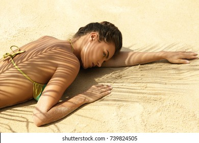Hot summer day. Beautiful woman is lying on the beach under palm leaf