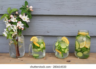 In hot summer day on the table decorated with apple tree blooms is served Naturally Flavored (Infused) Cucumber water with ice cubs, lemon, lime slides in Glass Jars