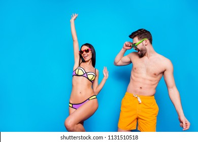 Hot summer time concept. Beach party style! Portrait of cheerful couple in sunglasses and bright swimsuits dance together raise their hands up isolated on bright blue background