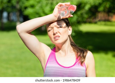 hot summer weather. girl covering her head from sunshine with hand in pain. young woman with bottle of water from thirst on sun. female female go sports get heat and sunstroke. Headache, feeling bad