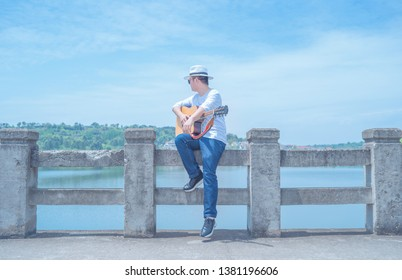 In a hot summer , a young literary youth who wearing a white T-shirt and jeans and a white Panama hat, plays the guitar alone on the dam under the blue sky.