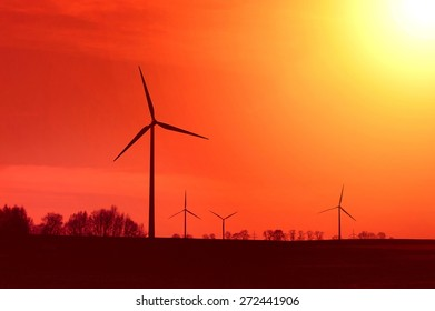 Hot sun and red sky over windmills. Alternative energy concept.