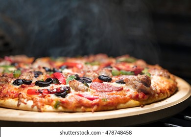 Hot supreme thin crust pizza cooking in oven with steam and smoke