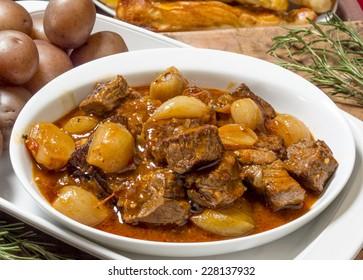 "hot and tasty bowl of greek beef stifado served with baby potatoes and fresh bread sticks  ""Greek beef Stifado"""