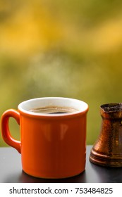Hot tasty coffee brewed in traditional turkish coffee pot, café