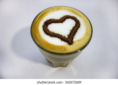 hot tasty coffee with foam decorated with heart